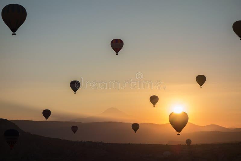 El aire caliente hincha en el cielo durante salida del sol Volando sobre el valle en Cappadocia, Anatolia, Turquía Montañas volcá fotos de archivo