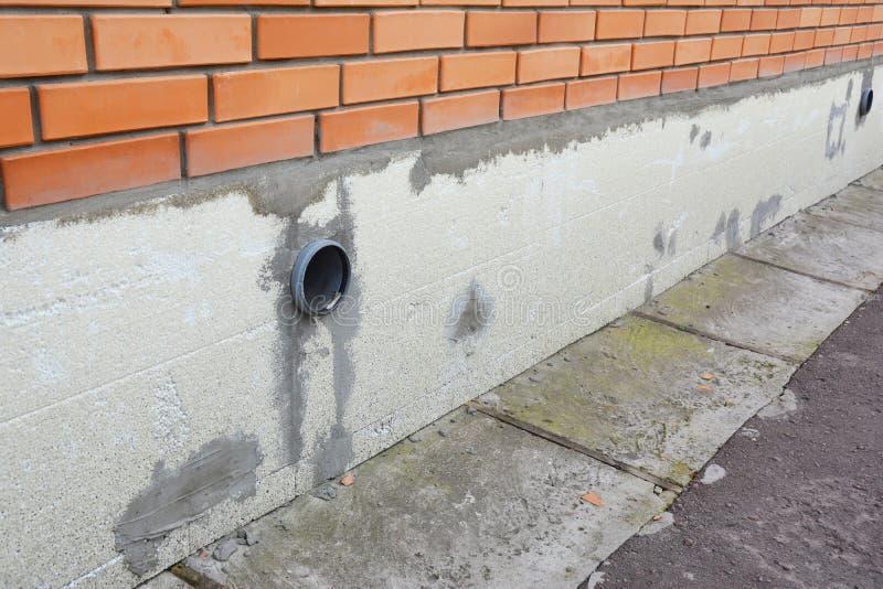 El aislamiento de la pared de la fundación de la casa del ladrillo con espuma de poliestireno cubre para el hogar ahorro de energ fotos de archivo libres de regalías