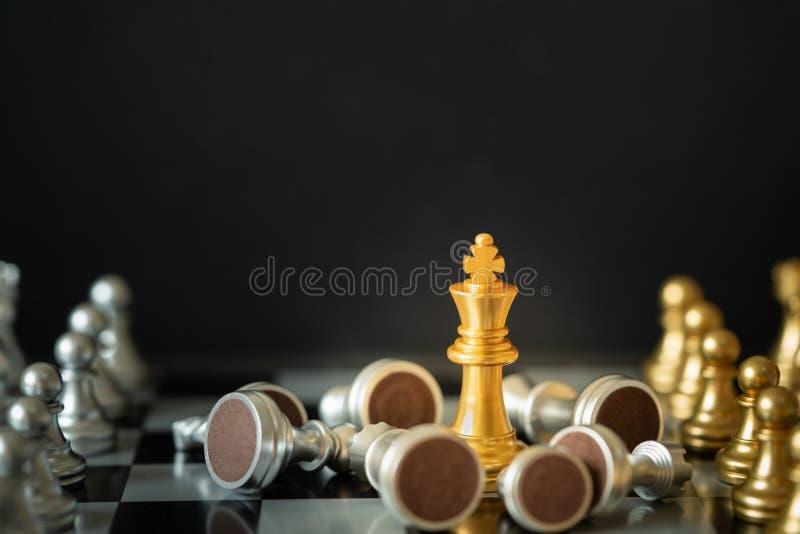 El ajedrez Gold King está en un tablero de ajedrez rodeado de oponentes de fondo oscuro foto de archivo