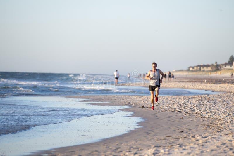 El ajuste atlético y el corredor fuerte sirven el entrenamiento en la playa de la puesta del sol del verano en el funcionamiento  fotografía de archivo libre de regalías