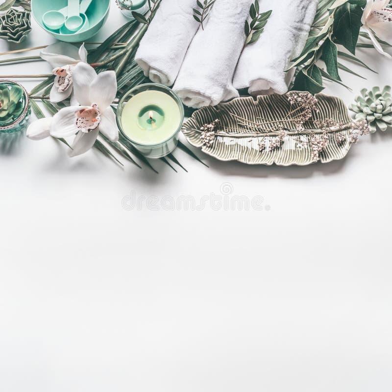 El ajuste con las toallas, vela verde, hojas tropicales, orquídea del tratamiento del balneario florece en el fondo blanco con el foto de archivo libre de regalías