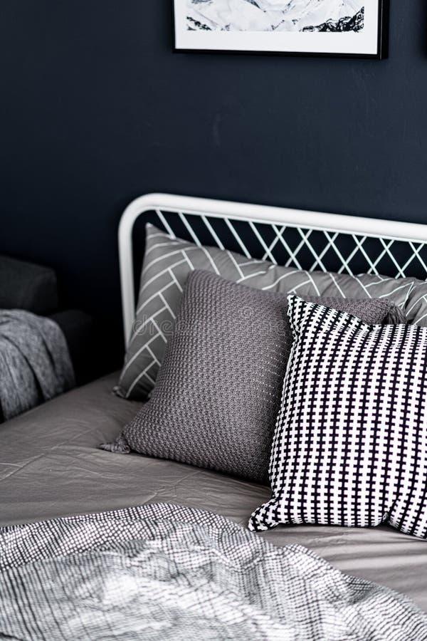 El ajuste de la esquina del dormitorio con las almohadas gráficas cómodas en color neutral con los azules marinos pintó interior  fotos de archivo