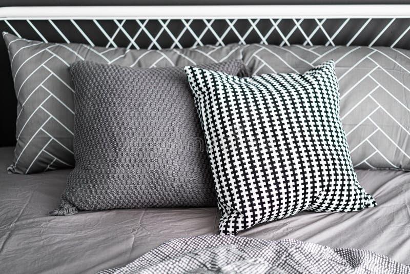 El ajuste de la esquina del dormitorio con las almohadas gráficas cómodas en color neutral con los azules marinos pintó interior  imagen de archivo