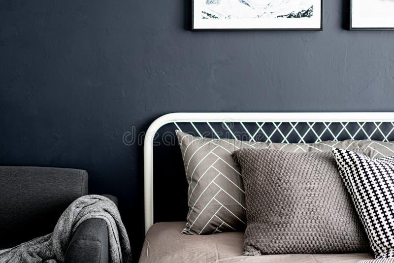 El ajuste de la esquina del dormitorio con las almohadas gráficas cómodas en color neutral con los azules marinos pintó interior  fotos de archivo libres de regalías