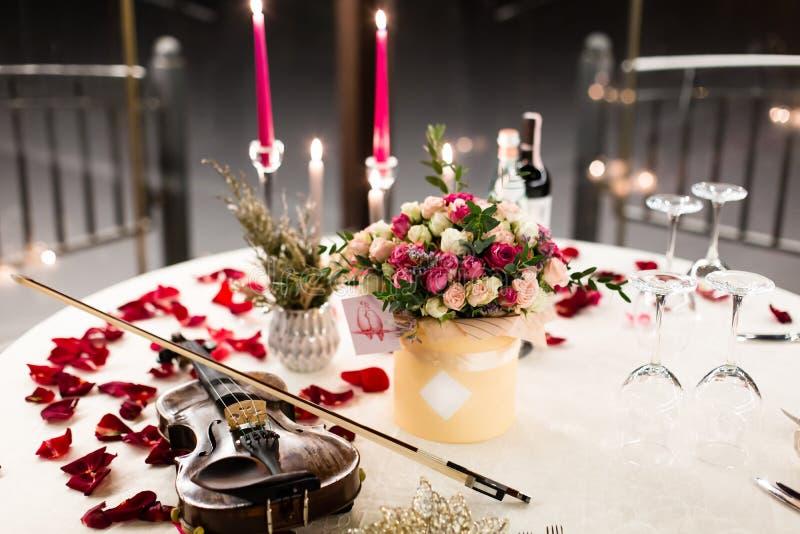 El ajuste romántico de la tabla con las flores hermosas en caja, subió los pétalos y violín imagen de archivo libre de regalías