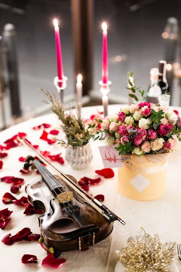 El ajuste romántico de la tabla con las flores hermosas en caja, subió los pétalos y violín fotografía de archivo libre de regalías