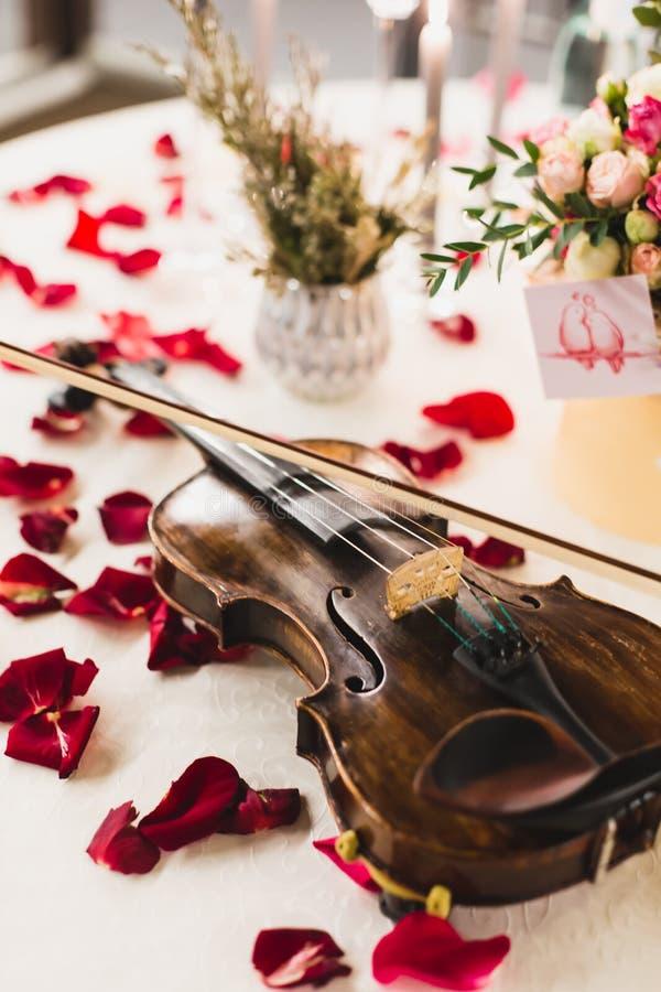 El ajuste romántico de la tabla con las flores hermosas en caja, subió los pétalos y violín imágenes de archivo libres de regalías