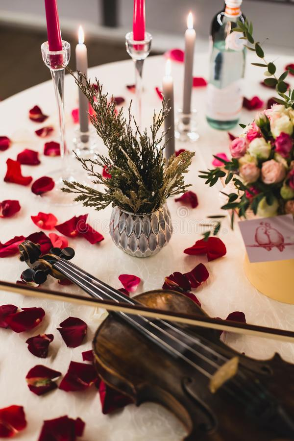 El ajuste romántico de la tabla con las flores hermosas en caja, subió los pétalos y violín imagenes de archivo