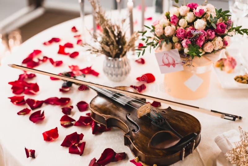 El ajuste romántico de la tabla con las flores hermosas en caja, subió los pétalos y violín foto de archivo