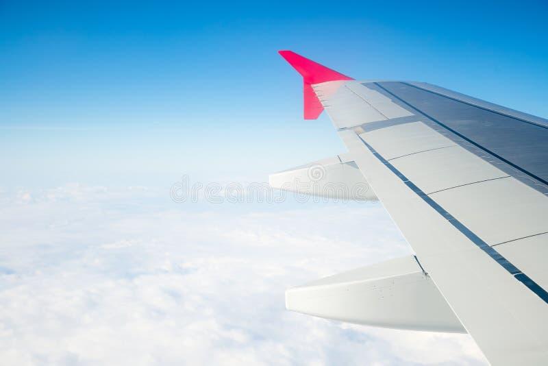 El ala de un vuelo del aeroplano sobre la ma?ana se nubla Ala de aviones en el cielo, mirando a través de la ventana imagenes de archivo
