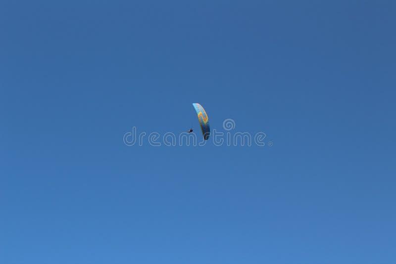 El ala flexible realiza figuras de las acrobacias aéreas arriba en el cielo azul imagen de archivo libre de regalías