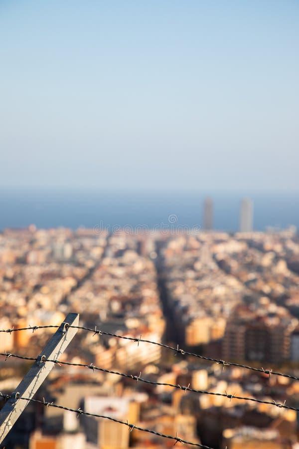 El alambre de púas enfocado con la ciudad de Barcelona empañó en fondo imágenes de archivo libres de regalías