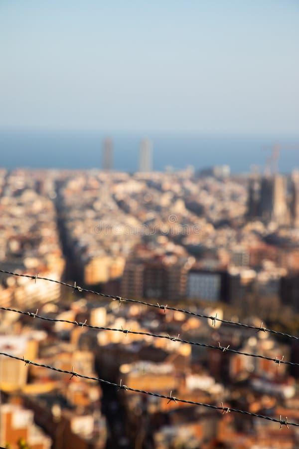 El alambre de púas enfocado con la ciudad de Barcelona empañó en fondo imagenes de archivo