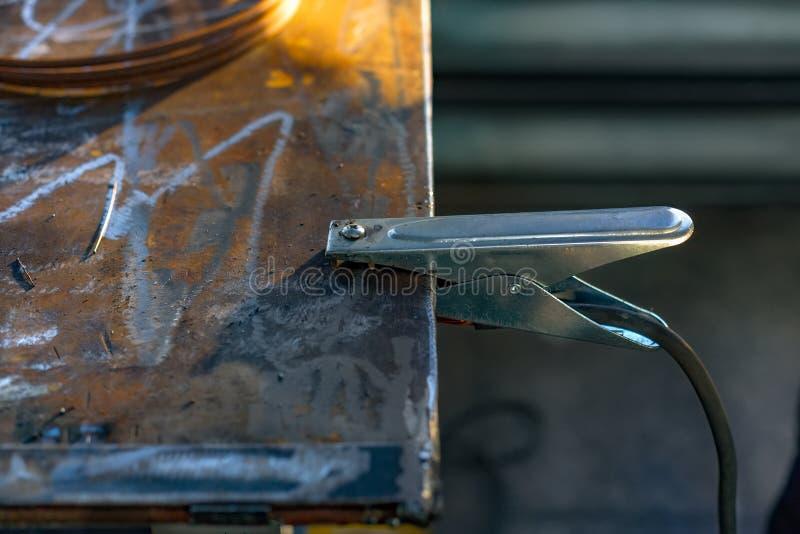 El alambre negativo de la soldadora con un perno se ata a la tabla del metal grounding imagen de archivo