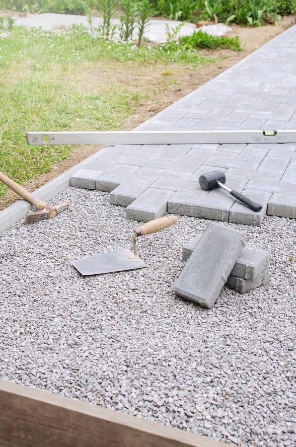 El albañil pone los bloques concretos de la piedra de pavimentación para acumular a imágenes de archivo libres de regalías
