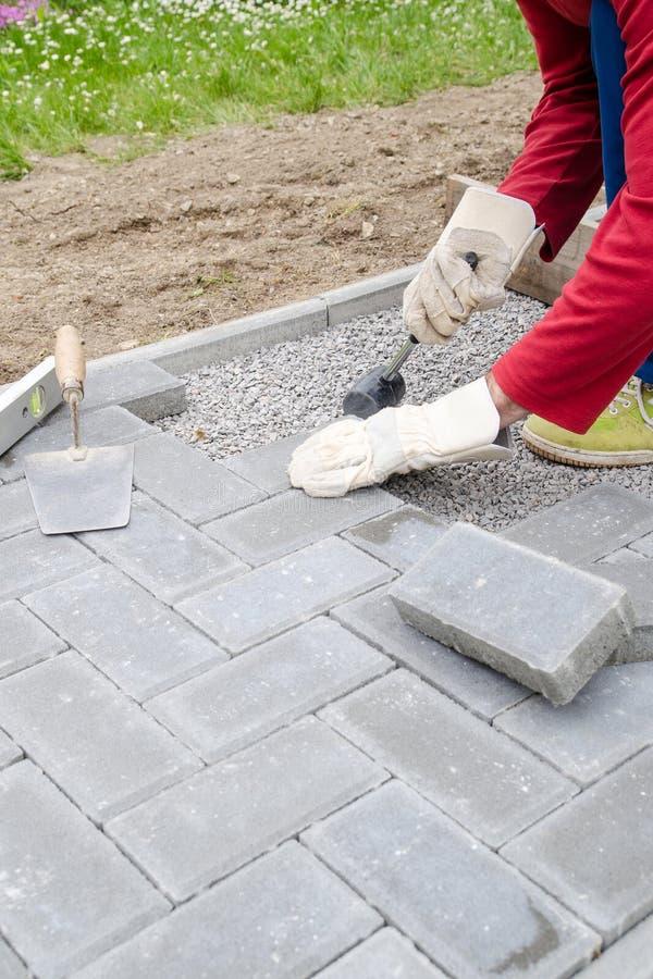 El albañil pone los bloques concretos de la piedra de pavimentación para acumular un patio, usando el martillo y el nivel de alco imagen de archivo libre de regalías