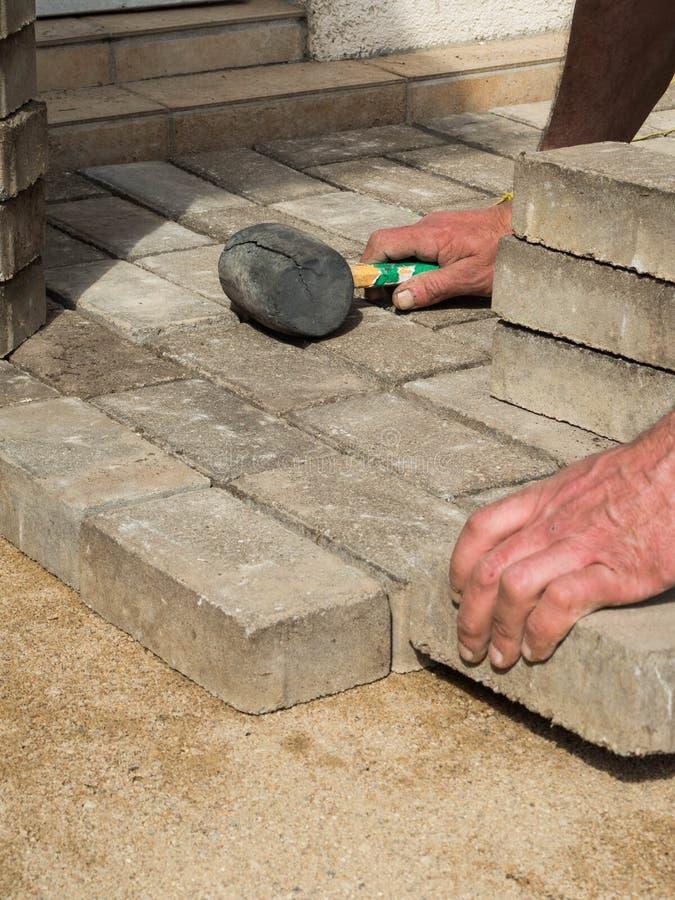 El albañil pone los bloques de piedra concretos de pavimentación para acumular una herramienta del martillo del patio fotografía de archivo