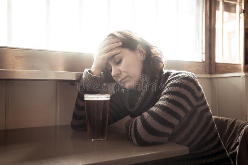 El alcoh?lico presion? a la mujer que beb?a en un desesperado triste de la sensaci?n de la barra foto de archivo