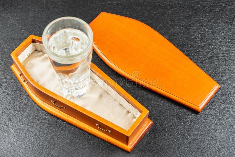 El alcohol está matando La consumición está matando a concepto Vaso de medida en ataúd fotos de archivo libres de regalías