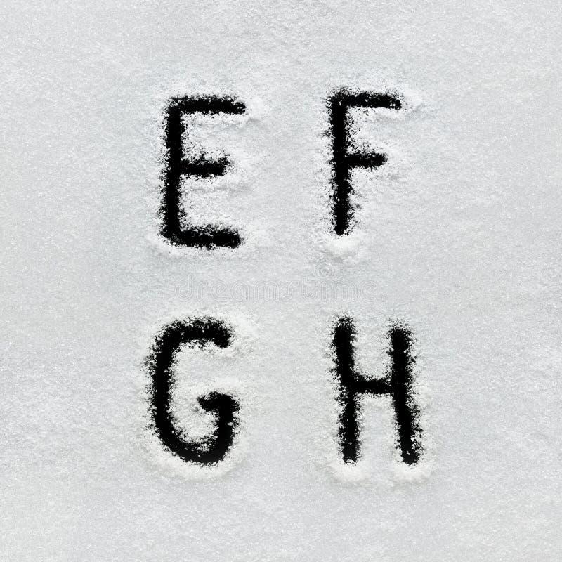 El alfabeto, los símbolos y los números del invierno dan escrito en nieve imagen de archivo libre de regalías