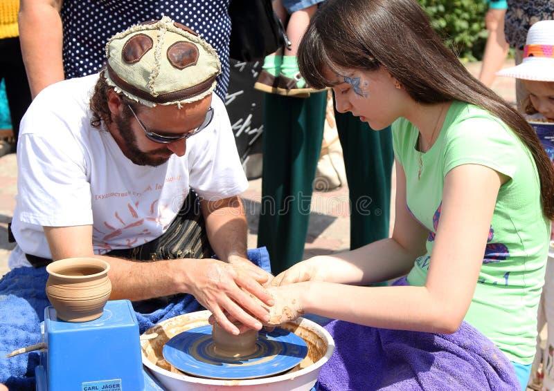 El alfarero da una lección a la muchacha en la fabricación de los productos de la arcilla imagen de archivo