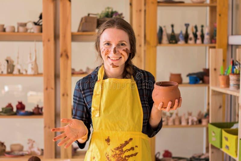 El alfarero sonriente hermoso n de la mujer el taller y sostiene el pote en sus manos foto de archivo