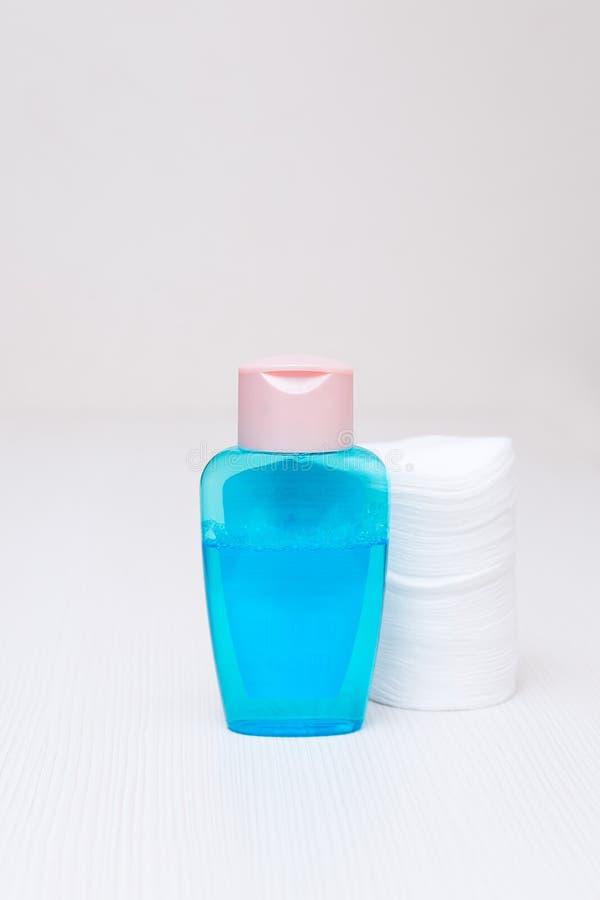 El algodón y la cara azul tónica se lavan en una tabla blanca en casa fotos de archivo