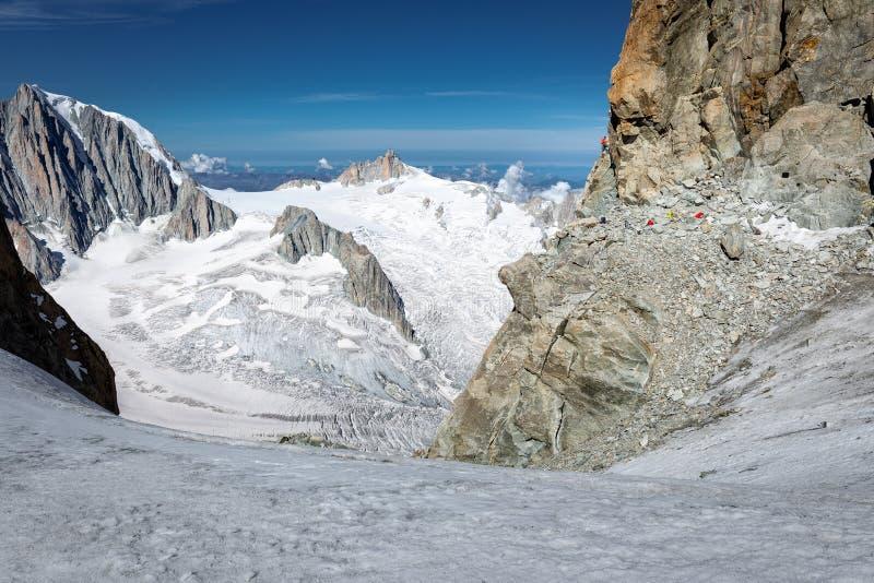 El alpinista que sube el acantilado de Dent du Geant, monta?as ajardina la visi?n imagen de archivo libre de regalías