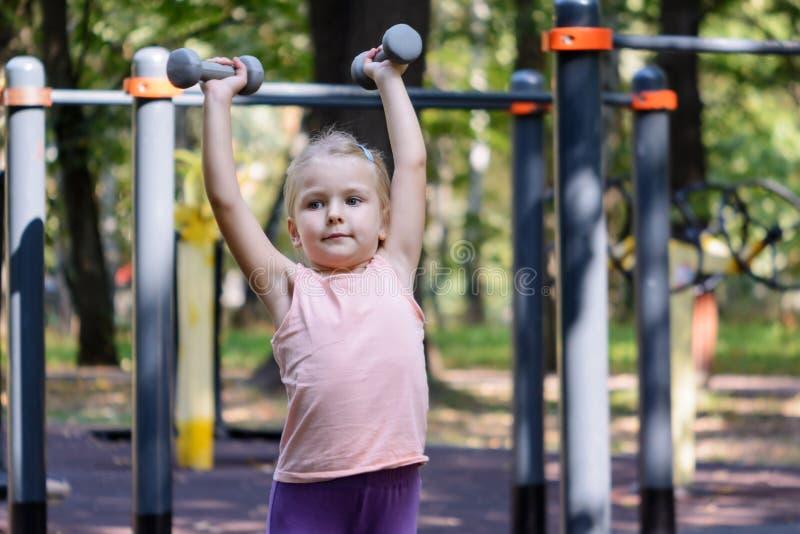 El alto del niño aumenta pesas de gimnasia Una niña con el pelo rubio entra para los deportes fotos de archivo