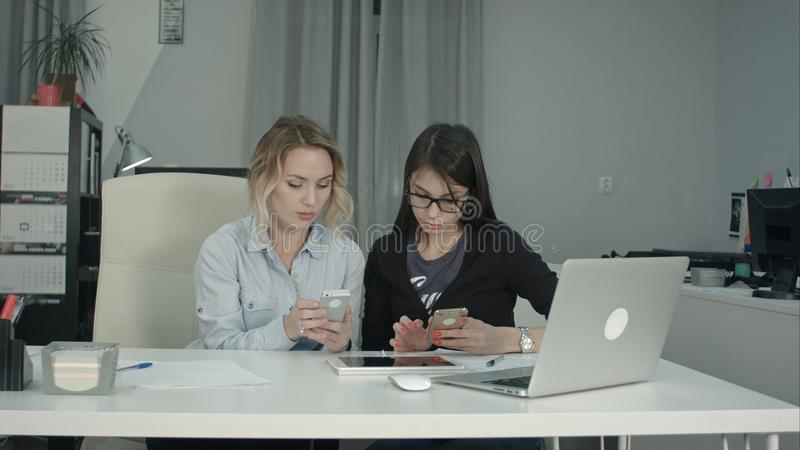 El alto directivo que muestra jóvenes interna en vidrios cómo utilizar el app móvil fotografía de archivo libre de regalías