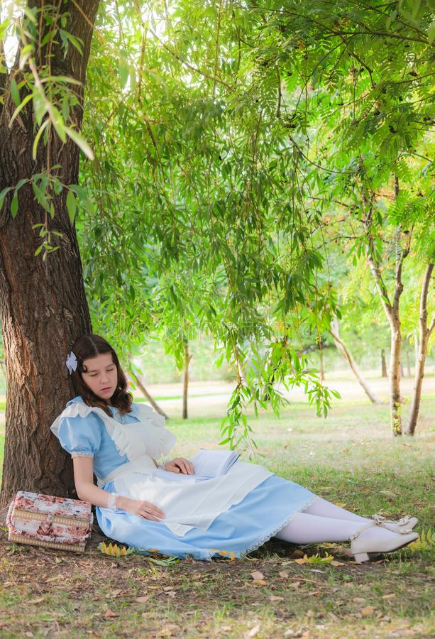 El alumno de la muchacha cayó sueño debajo de un árbol con un libro fotografía de archivo