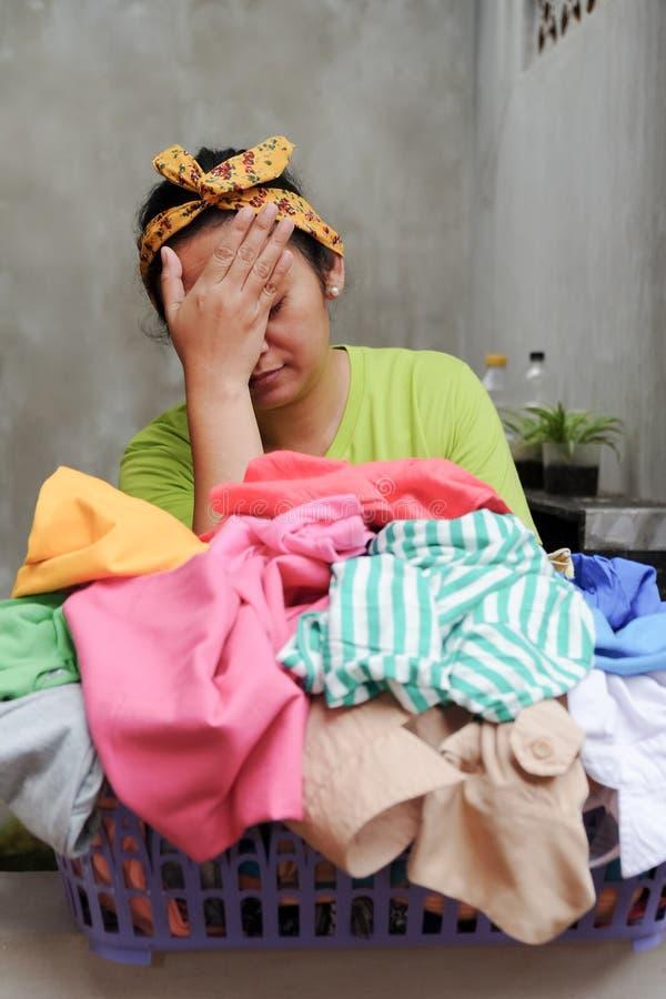 El ama de casa étnica asiática subrayó con trabajo diario del lavadero imagenes de archivo