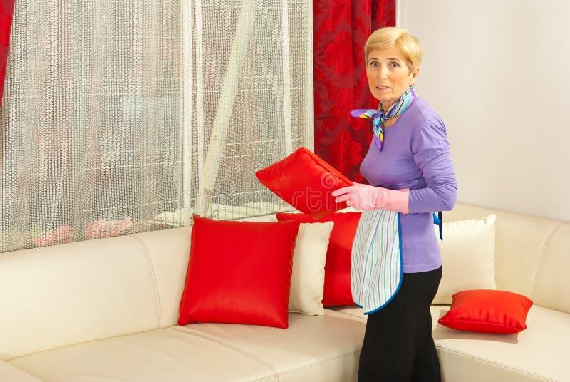 El ama de casa arregla las almohadillas en el sofá foto de archivo libre de regalías