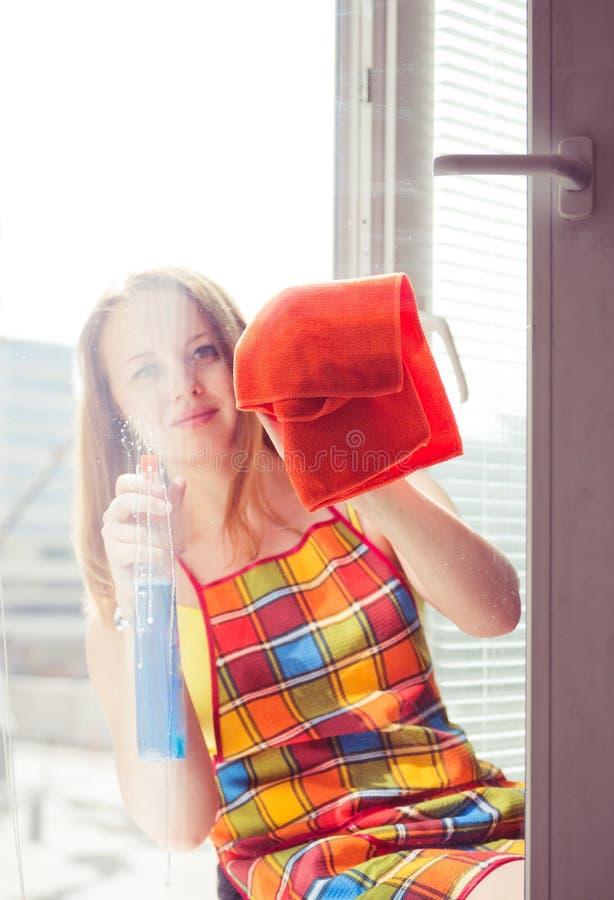 El ama de casa de la mujer lava una ventana imagenes de archivo