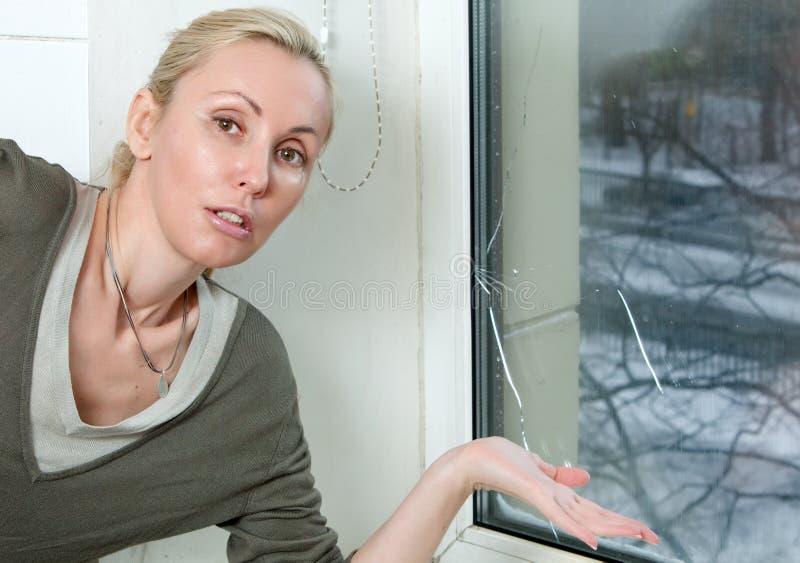 El ama de casa en la ventana quebrada foto de archivo libre de regalías