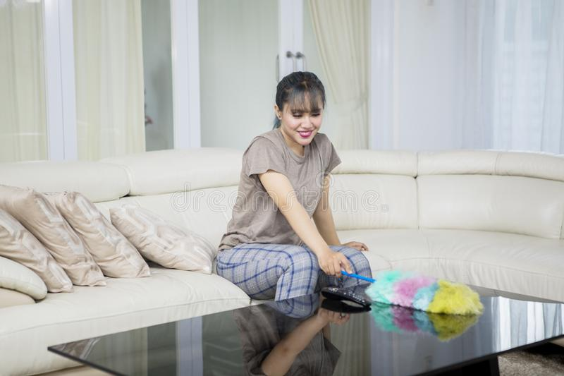 El ama de casa limpia la tabla con un cepillo del plumero fotos de archivo