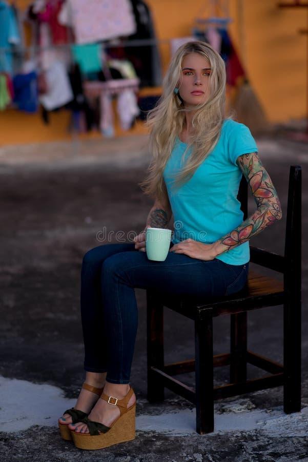 El ama de casa moderna que se sienta en la silla en el lino de la ejecución del fondo Especie condenada La mujer moderna fotografía de archivo libre de regalías