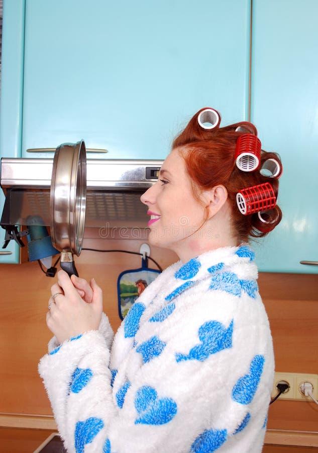 El ama de casa pelirroja joven en cocina cuesta y mira la reflexión en un sartén y sonríe fotografía de archivo