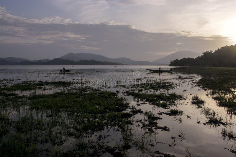 El amanecer en el lago, los pescadores vietnamitas de pesca redes imagen de archivo