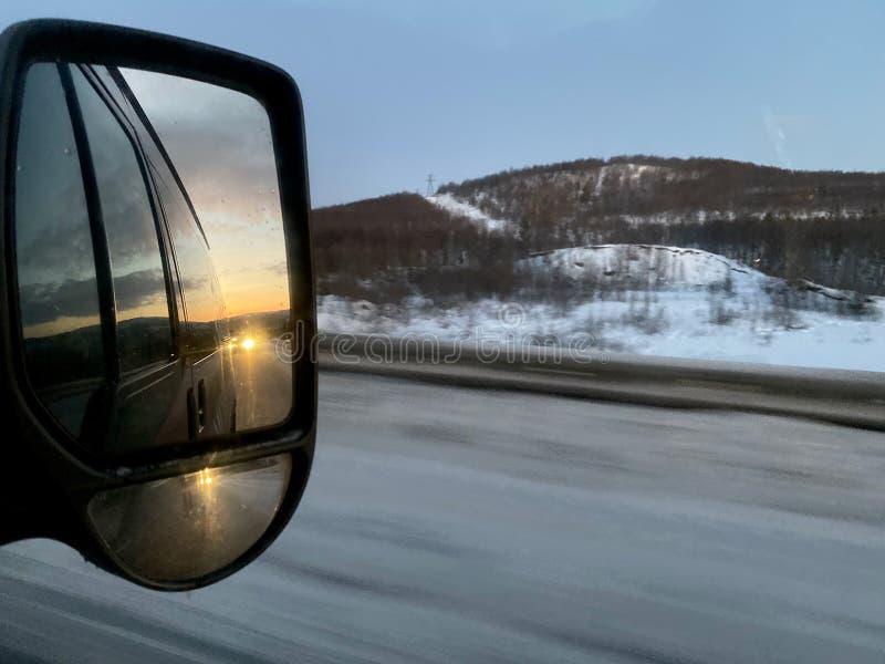 El amanecer por la mañana refleja el espejo interior del lado del auto durante el viaje por carretera en invierno fotografía de archivo libre de regalías