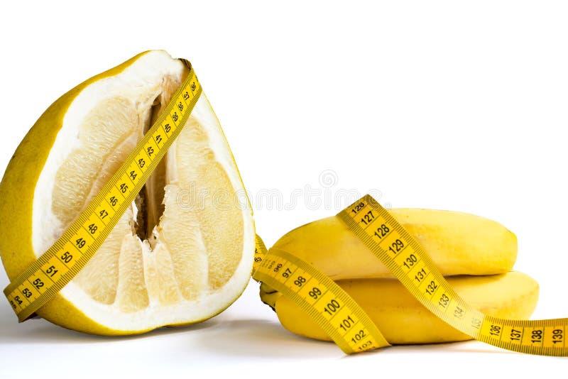 El amarillo cutted el pomelo crudo fresco y dos plátanos con la cinta de la medida alrededor imagen de archivo libre de regalías