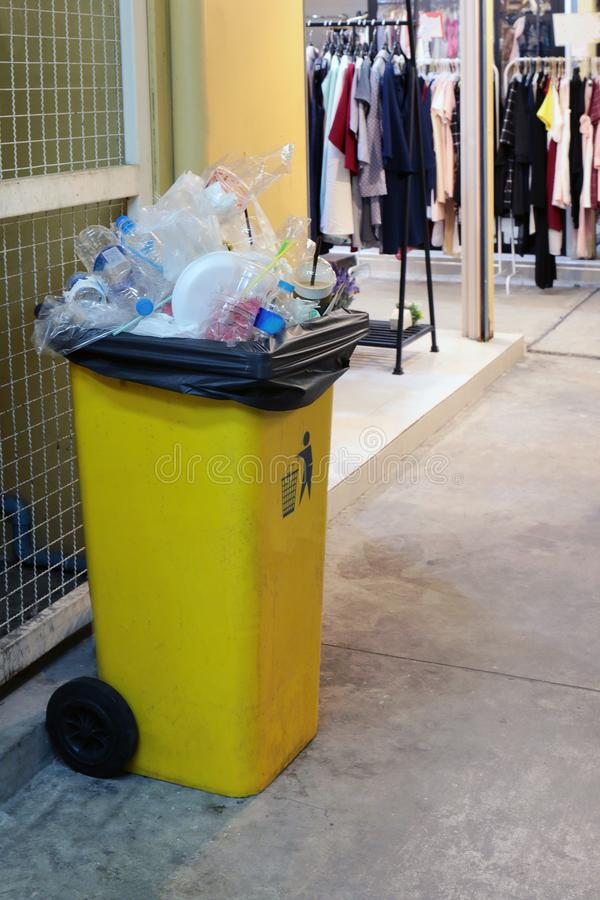 El amarillo plástico del compartimiento para la basura de la basura en la tienda de la tienda de la calzada, basura del cubo de l imagen de archivo libre de regalías