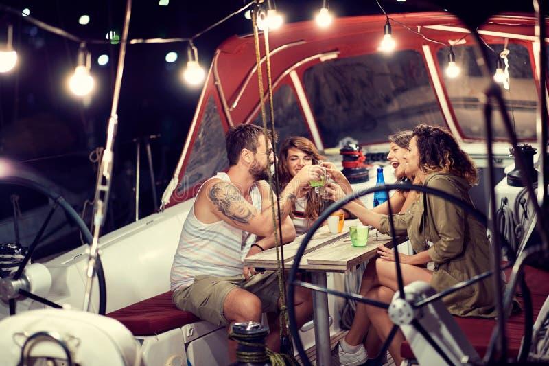 El amigo en el barco tiene partido en noche que sorprende foto de archivo