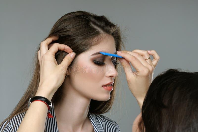 El amo corrige las cejas del modelo antes de tirar imagen de archivo