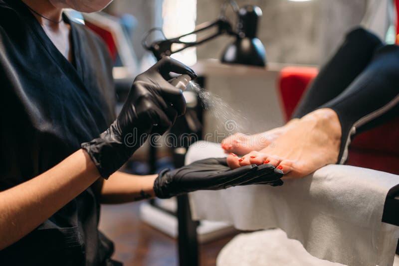 El amo de la pedicura rocía clavos del pie del cliente femenino fotos de archivo