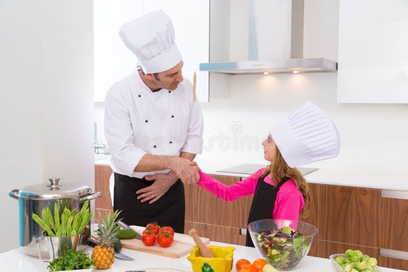 El amo del cocinero y el alumno menor embroman el apretón de manos de la muchacha foto de archivo libre de regalías