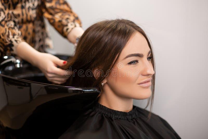 El amo del corte de pelo lava el pelo de su cliente ten?a imagenes de archivo