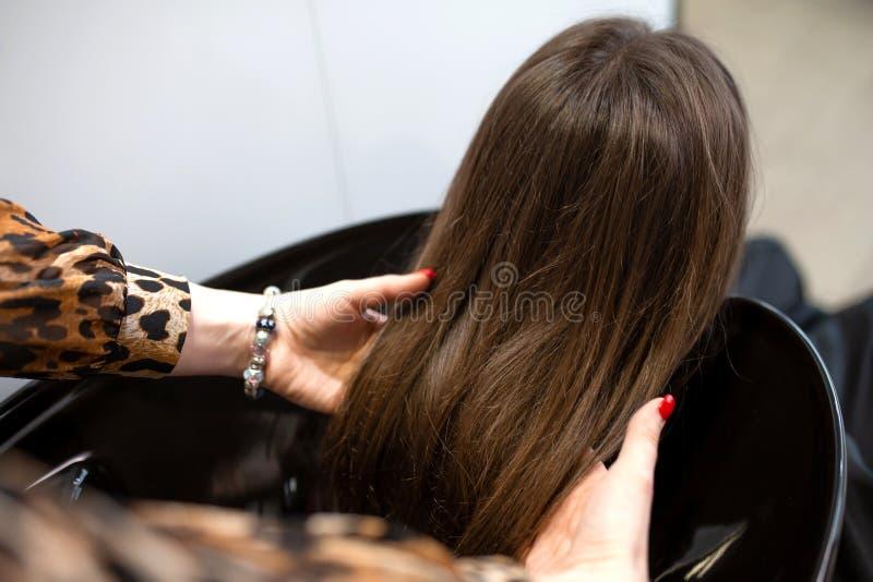 El amo del corte de pelo lava el pelo de su cliente ten?a fotos de archivo libres de regalías