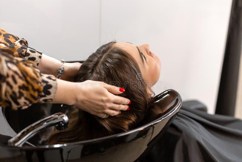 El amo del corte de pelo lava el pelo de su cliente ten?a foto de archivo