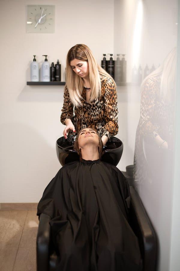 El amo del corte de pelo lava el pelo de su cliente ten?a imágenes de archivo libres de regalías